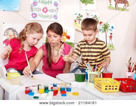 Children with teacher painting in play room. Preschool.