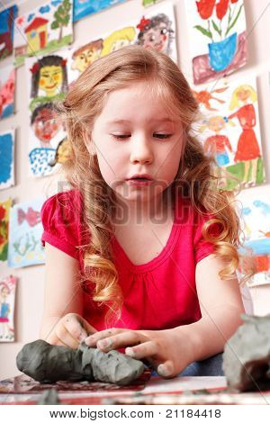 Child girl play clay in play room. Preschool.