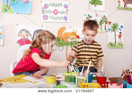 Children painting in play room. Child care.