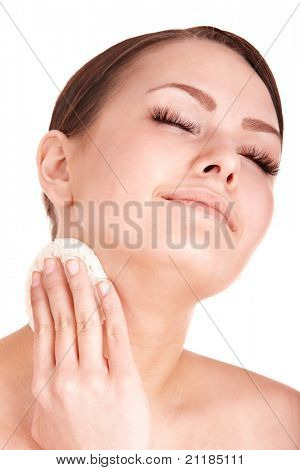 Young woman washing her face by sponge. Isolated.