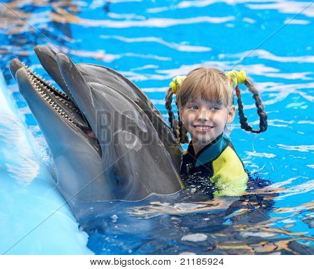 Happy child and dolphin in blue water.