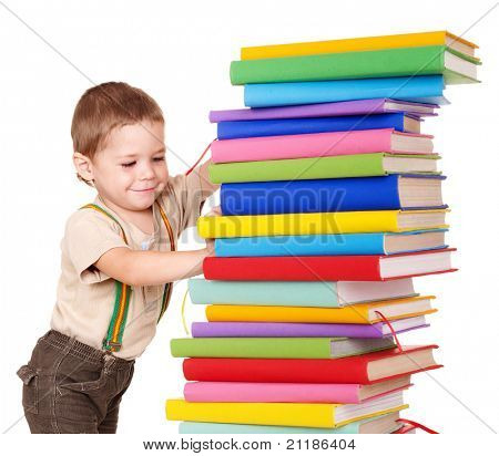 Little boy reading pile of books.