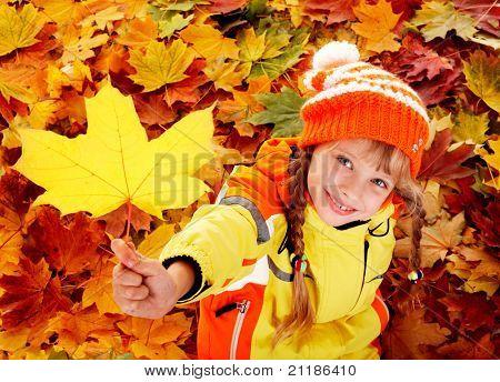 Niña en otoñales hojas de naranja. Al aire libre.