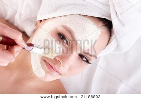 junge Frau mit Ton-Gesichtsmaske.