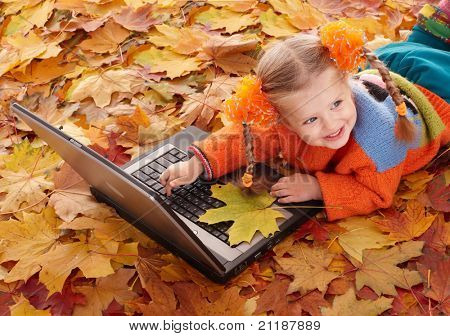 Little girl in autumn orange leaves with laptop. Outdoor.