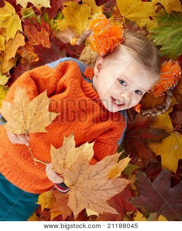 Little girl in autumn orange hat on leaves and gift box. Outdoor.