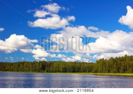 Lake In-Field. A Bright Summer Sun. White Clouds Overwater.