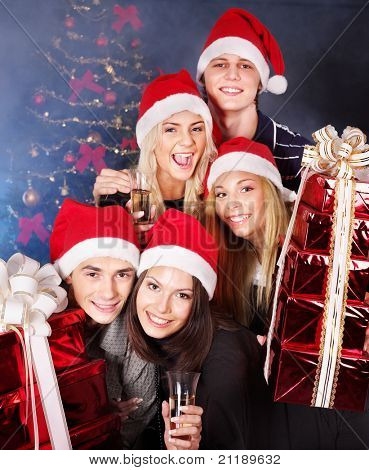 Group  people in santa hat holding stack gift box at nightclub.