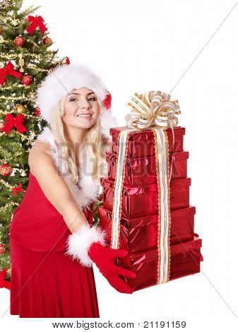 Girl in santa hat giving stack red gift box by christmas tree. Isolated.