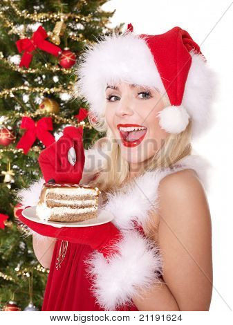 Christmas girl in red santa hat eat cake on plate. Isolated.