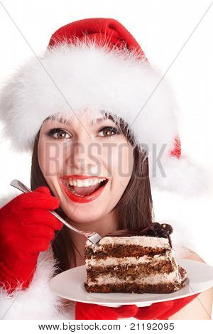 Christmas girl in red santa hat eating cake on plate. Isolated.
