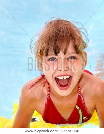 Children  on inflatable ring in swimming pool.