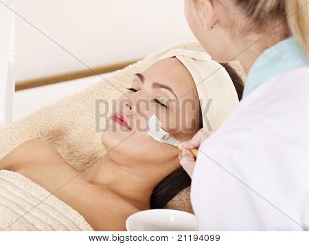 Beautician applying  facial mask by young woman.