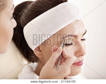 Tweezing eyebrow by beautician. Isolated.