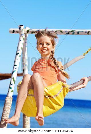 Happy little girl swinging on  swing .