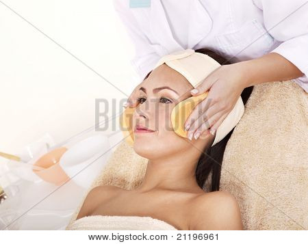 Young woman washing  face by sponge.