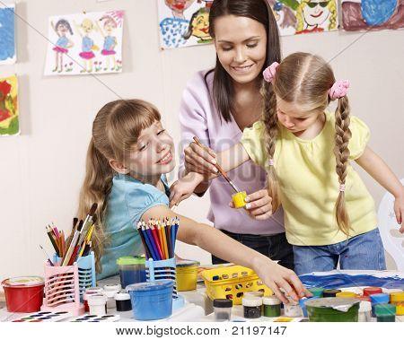 Child painting in preschool. Teacher help by little girl.