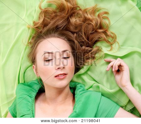 Sleeping young woman in green dress.