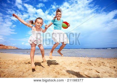 Menina brincando na praia com bola.