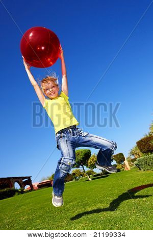 Child playing in park with ball. Outdoor.
