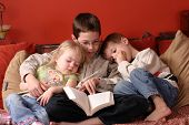pic of storytime  - 3 children at home reading a book together - JPG