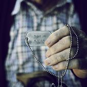 closeup of an old caucasian man showing a dog tag with the text thank you veterans engraved in it poster