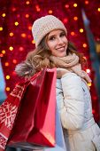 Woman shopping for Christmas. Young happy woman holding christmas decorated shopping bags in front o poster