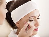 stock photo of beauty parlour  - Tweezing eyebrow by beautician - JPG