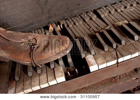 Old Dirty Piano With Old Leather Shoe