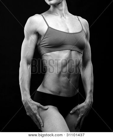 Black and white image of a muscular female body against black background.