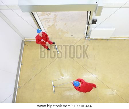Overhead view of two workers in red uniforms and blue hardhats cleaning floor in industrial building