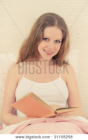 Beautiful Blonde Girl Reading A Book  In Bed
