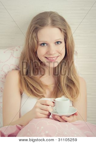 Beautiful Young Woman With Cup Of Morning Coffee In Bed