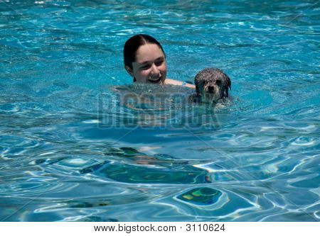 Girl And Dog Swimming In Pool