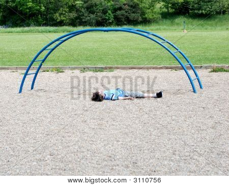 Boy Laying Beside Playground Equipment.