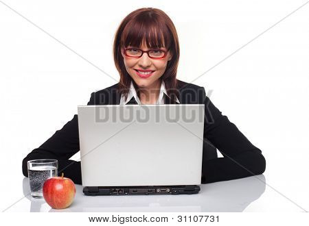 Healthy businesswoman seated at her desk in front of her laptop with a glass of fresh clean water and an apple