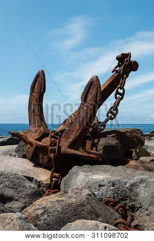 poster of Old Rusted Anchor With A Chain, Exposed In The Harbor Area On The Rocks On The Coastline Of Atlantic