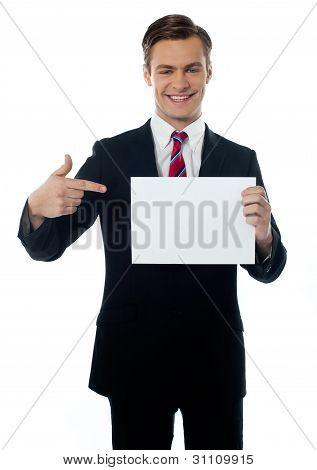 Young Salesman Pointing Towards Blank Billboard