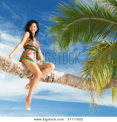 Fashion woman siting upon palm tree