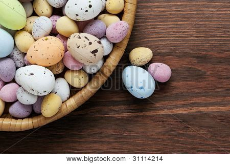 Still life photo of speckled candy covered chocolate easter eggs in a wicker basket on a rustic wooden table.