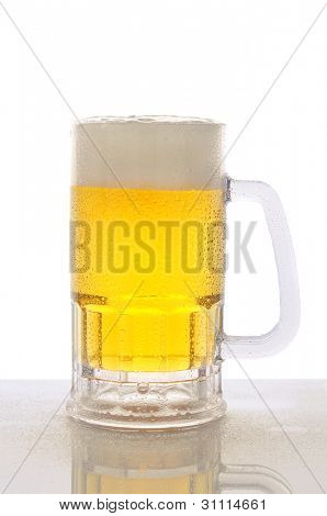 A cold frosty mug of beer on a wet bar counter top with a white background. Vertical format with reflection..