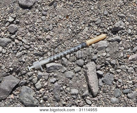 Discarded drug addict needle syringe in the dirt.