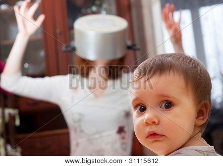 Retrato de bebé asustado contra madre loco con pan en cabeza