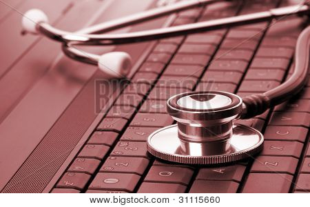 Medical stethoscope on laptop keyboard. Toned in red