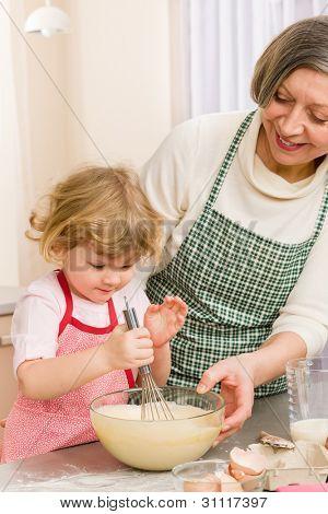 Grandmother and granddaughter baking cookies prepare dough