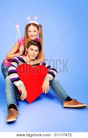 Amor joven pareja posando junto con corazón rojo.