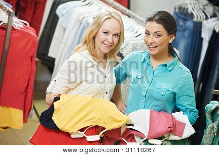 Two Young women with apparel shirt or blouse during garments clothing shopping at store