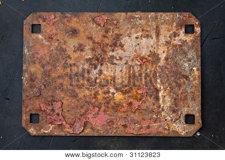 Rusted metal plate on dirty reason