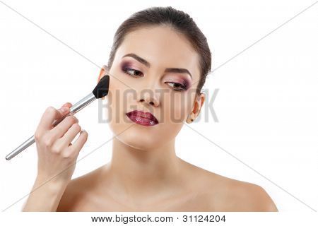 beauty portrait of young beautiful woman with hand of esthetician applying rouge with brush isolated on white background
