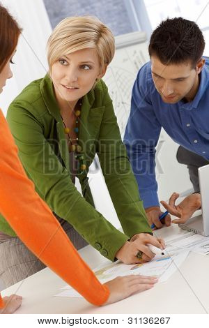 Smiling coworkers brainstorming, using notes, working together, standing at meeting table.